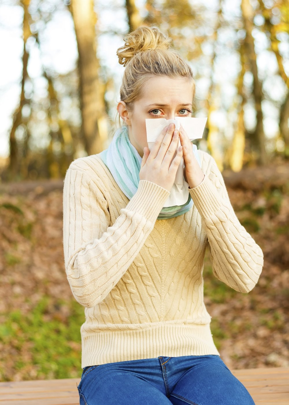 Blonde woman blowing nose.jpg