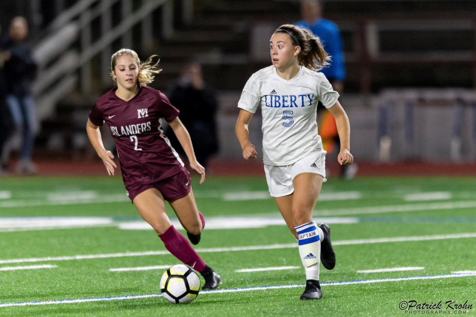 Mercer Island senior midfielder Emily Arron, left, puts pressure on Liberty defender Cameron Nelson, right, in a matchup featuring two of the top soccer programs in the 3A/2A KingCo Division. Mercer Island earned a 2-1 comeback victory on Sept. 25 on Mercer Island. Photo courtesy of Patrick Krohn/Patrick Krohn Photography