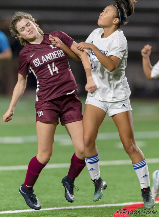 Mercer Island senior Ella Hensey, left, battles with Liberty defender Kelsey Le, right, for possession of a 50/50 in the air. Photo courtesy of Patrick Krohn/Patrick Krohn Photography