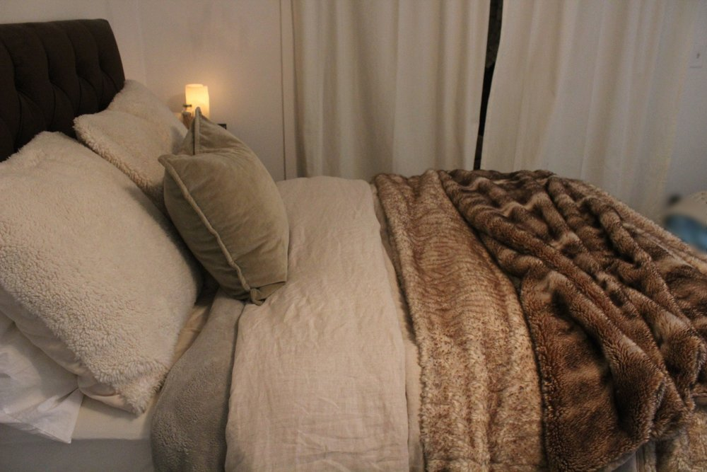 WINTER - Start with a cozy fleece blanket, then add a fluffy neutral duvet across the whole bed and top it off with some faux fur blankets. The standard sleeping pillows are tucked behind two euro sized pillows with faux sheepskin covers and then a 20