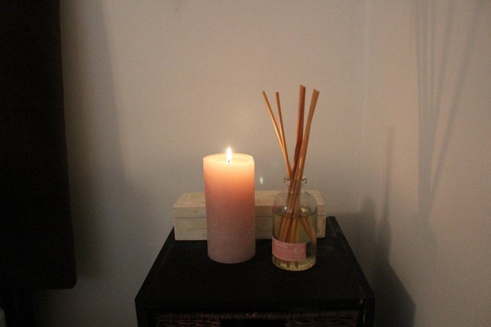 SPRING - A small pink candle adds color to the bedside table and a honeysuckle diffuser brings a fresh spring scent to the bedroom.
