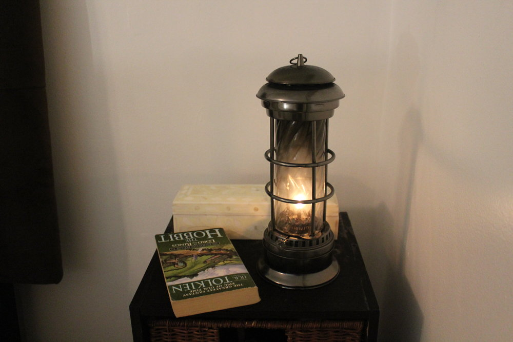 FALL - A kerosene lantern, ivory bone box and a good book creates a welcoming and cozy bedside table.