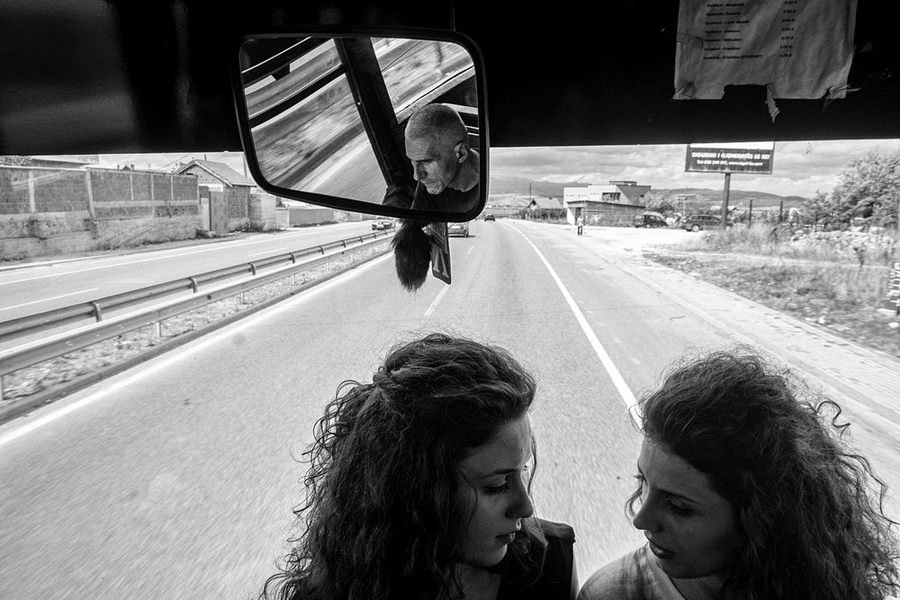 Two Albanian girls are traveling by bus to school in Dakovica-Gjakova, a city on the border and a center of Sufi spirituality.