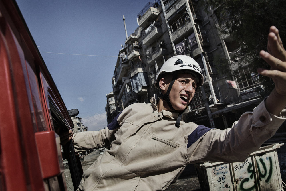 A young rescue worker, and member of the Civil Defense Team, reacts to a nearby air strike by the Syrian Regime in Aleppo. June 18, 2014.