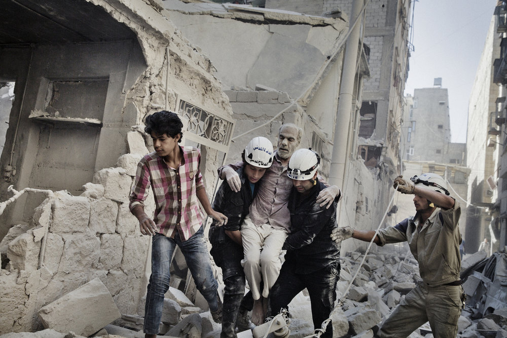Civil Defense members rescue a man who had been trapped inside his home after a barrel bomb collapsed it. June 20, 2014