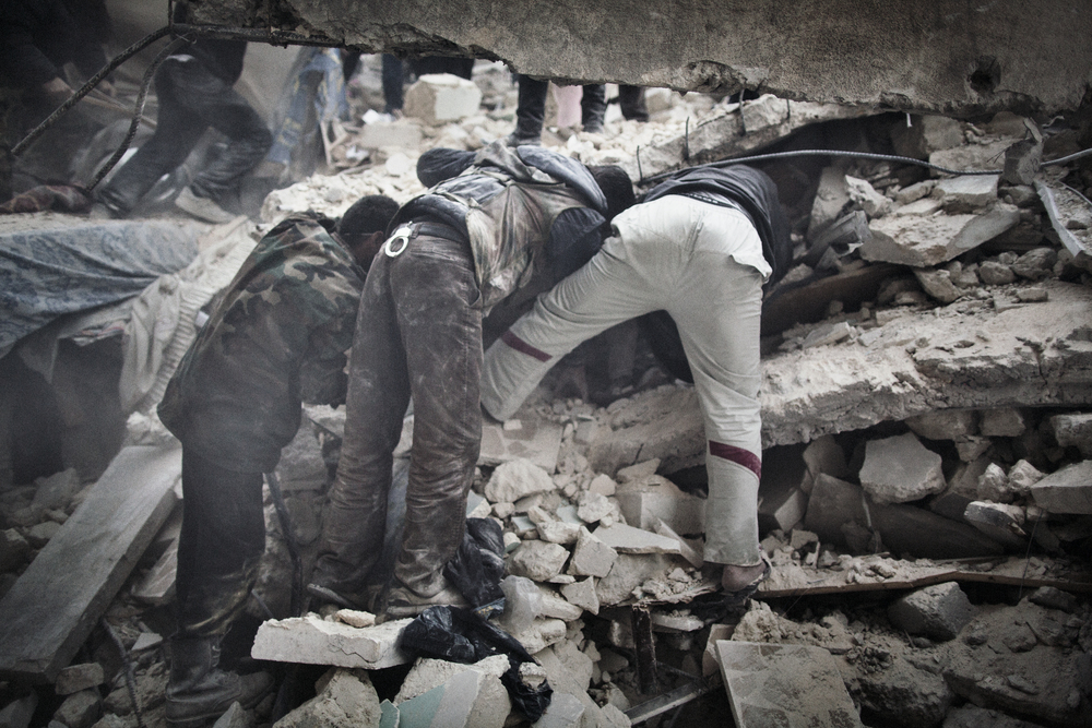 Civil Defense and Free Syrian Army fighters join forces in search for survivors amongst the rubble of a collapsed building that was struck by a regime airstrike. June 22, 2014.