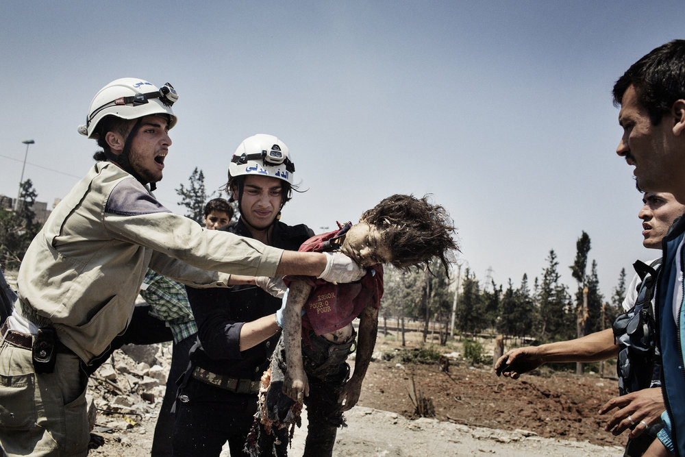 Members of the Civil Defense team remove the dead body of an 8 year old child from a car destroyed by a regime barrel bomb. June 19, 2014.