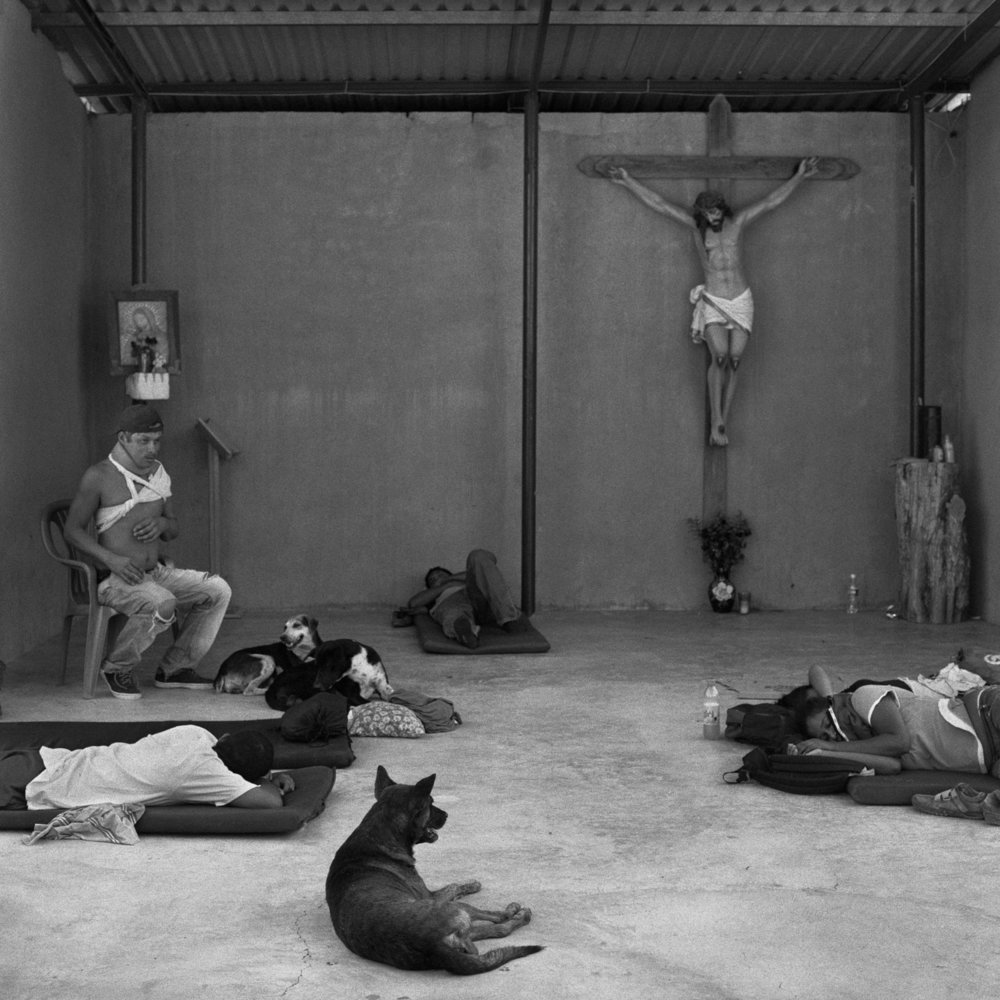 Weary and injured migrants rest in a makeshift chapel at the Hermanos en El Camino migrant shelter, in the small town of Ixtepec, Oaxaca. June 2009.