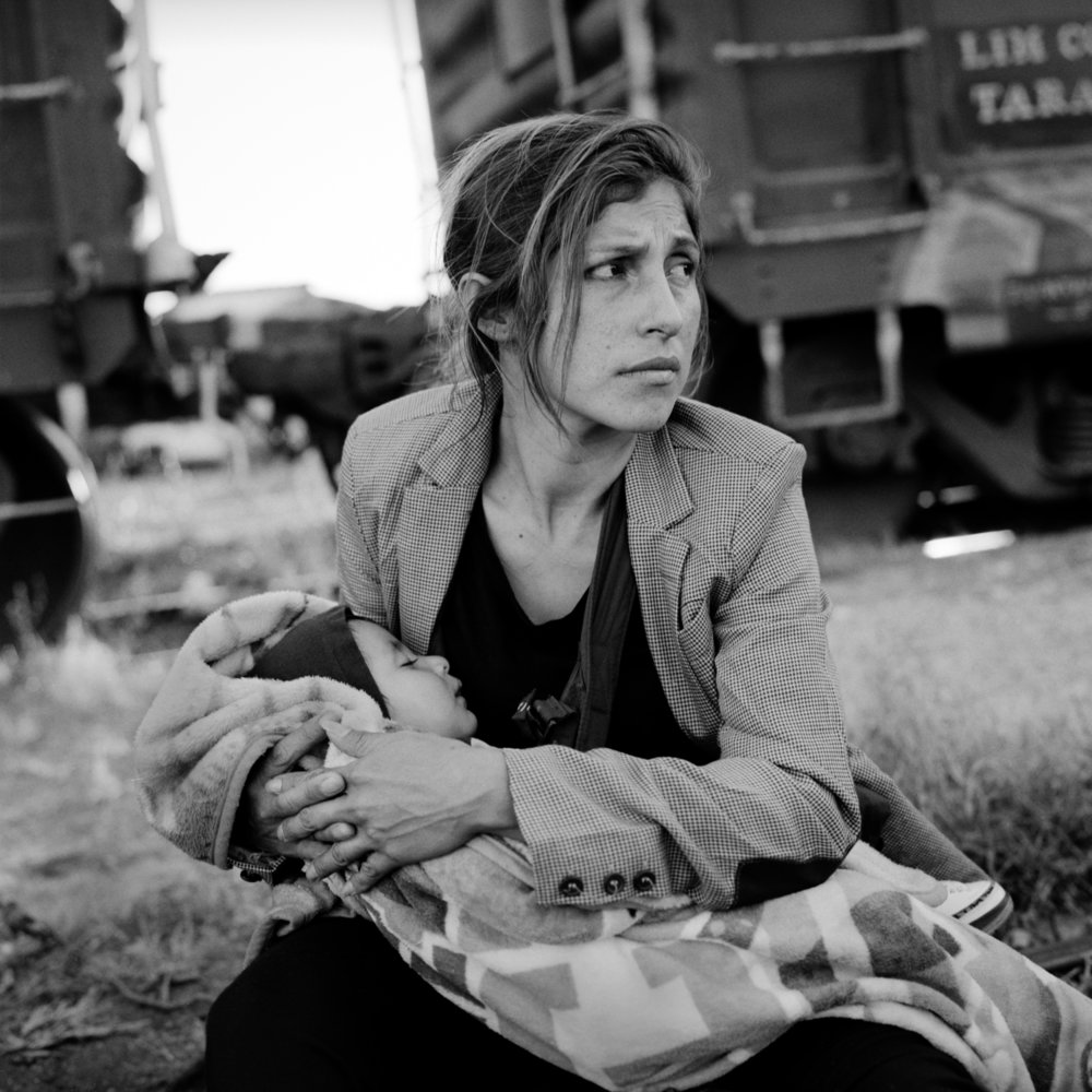 A Guatemalan woman fleeing an abusive husband holds her infant son while waiting for a northbound cargo train in the railhead town of Arriaga, southern Mexican state of Chiapas. January 2014.