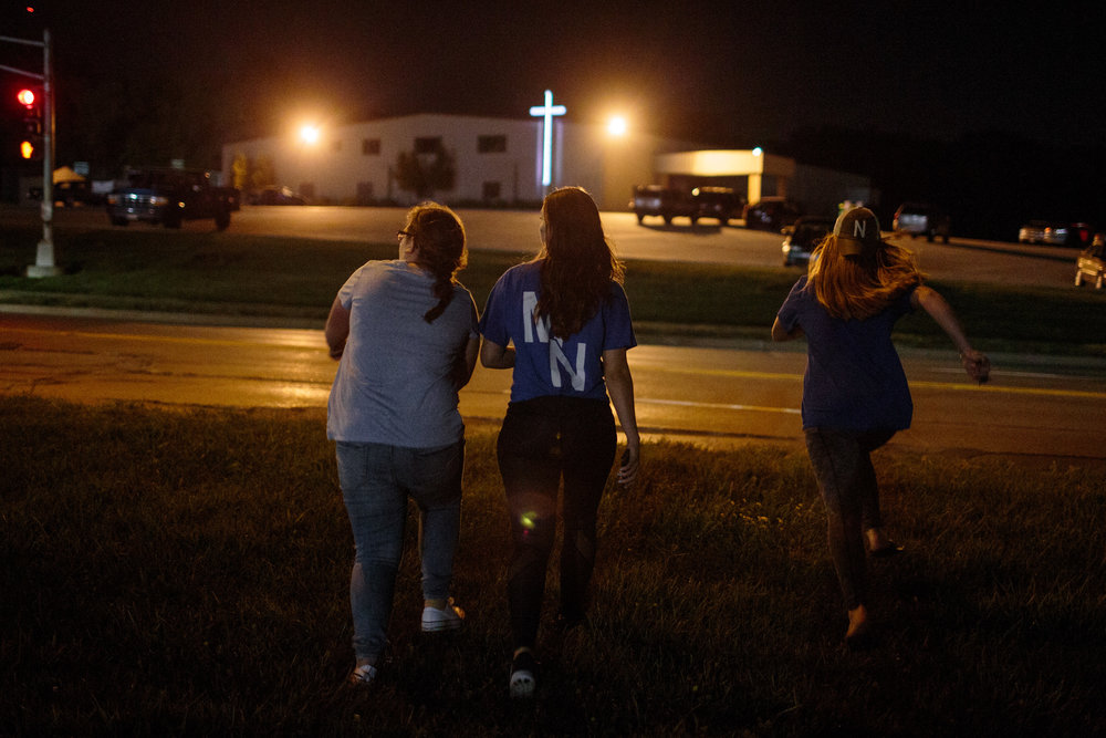 Megan, Stephanie, and Elizabeth, high school seniors, run to their cars, parked in the church parking lot across the street from the high school, after losing their first football game of the season, 25 August 2017, Omaha, Nebraska. Elizabeth Nelson, 17, spends the evening celebrating with her friends during their senior year. She enlisted to the army the summer before her senior year of high school, and will ship out to boot camp three days after she graduates.