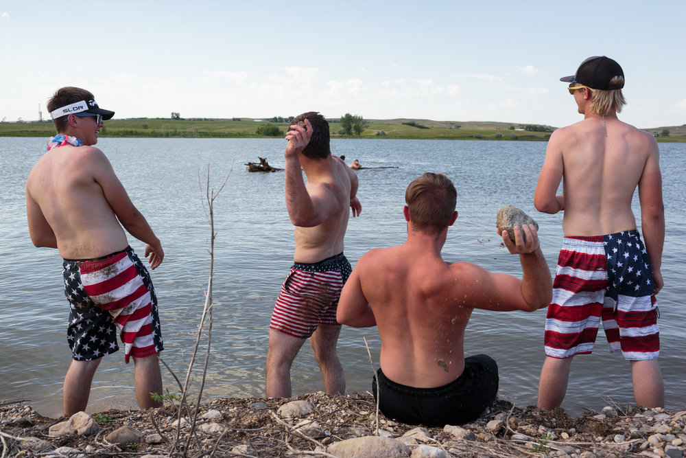 Jamison, Jade, Gregory and Nick, throw rocks at their friends swimming in the distance, celebrating the 4th of July holiday on the Fort Berthold Reservation, 3 July 2017, North Dakota. The group is saying goodbye to one of their friends, Logan, who leaves in two days for boot camp for the Marines. His grandpa inspired him, and he didn't want to work on the oil fields.