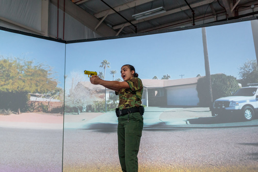 "Nerisa Garcia, a student from the Border Patrol Explorer Program, practices with the ""Virtu 300,"" a reality program helping train individuals in law enforcement in real-life scenarios with active shooters, at the United States Border Patrol Station in Kingsville Texas Station, 19 July 2017. The Explorer program is sponsored by Boy Scouts and Homeland Security, and nearly 700 students, ages 14-20, participate at their local Border Patrol post."