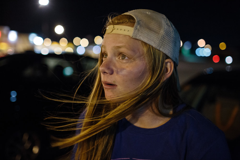 "Elizabeth Nelson, 17, waits in the parking lot of Home Depot waiting for her friends after watching their team their first football game of the season, 25 August 2017, Omaha, Nebraska. . Nelson enlisted to the army the summer before her senior year of high school, and will ship out to boot camp three days after she graduates. ""I feel like Omaha is not really the place for me. So, I definitely want to move out West if anything. I do kind of want to get the hell out of here."""