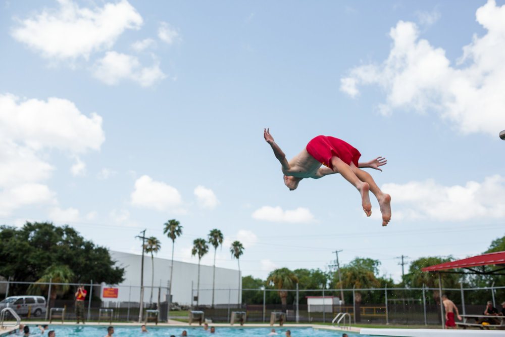 A student dives into a pool on a hot, 100 degree Texas afternoon at Marine Military Academy, an all-boys institution. MMA hosts a summer camp on their academic campus in Harlingen, Texas, 17 July 2017. The camp hosts boys from around the world, ages 12-18, with around 300 cadets in attendance.