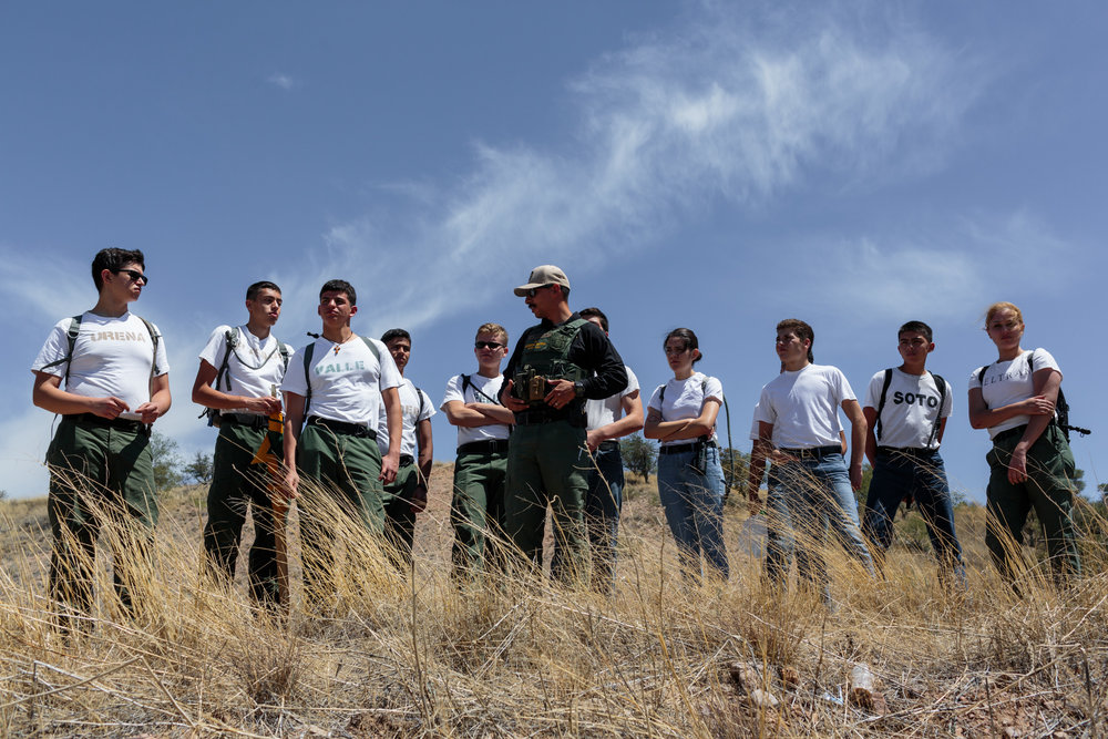 "On the third day of an Academy Week, students from the Border Patrol Explorer program go on a geographic orientation tour, Nogales, AZ, 1 June 2017. The tour shows the students the west and east sides of the border wall, and instructs them how to identify landmarks in their landscapes, how to map their route, and make proper directions via radio. The ""Explorer"" program offers 14-20 year olds the opportunity to work with law enforcement and experience what it is like to work as a border patrol agent."