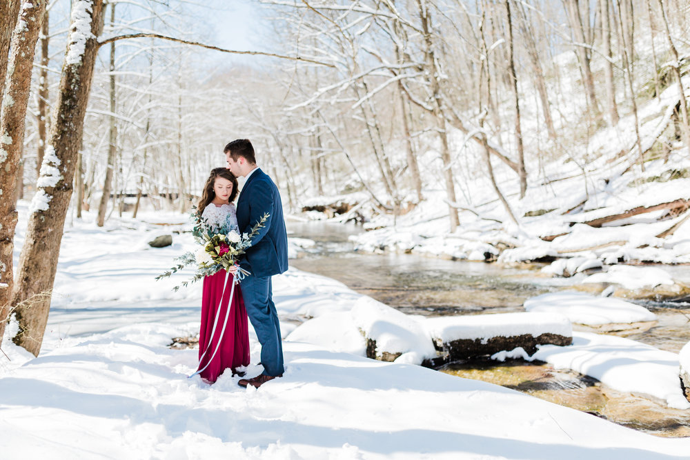 couple in snow with bouquet and maxi skirt for winter engagement session in westminster maryland