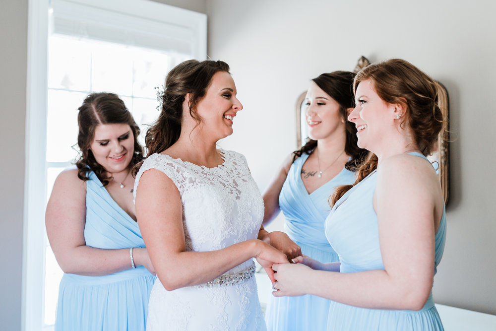 Bride and bridesmaids getting ready and laughing