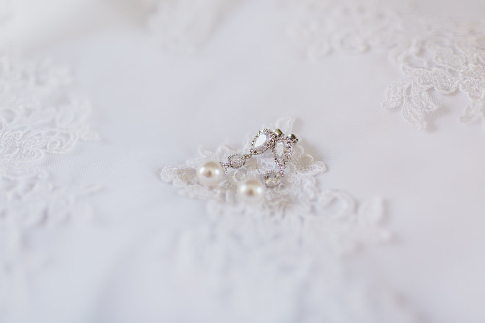 Bridal details of teardrop earrings laying on wedding gown