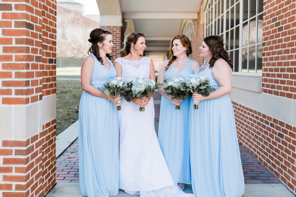 bride and her bridesmaids laughing for portraits with their bouquets