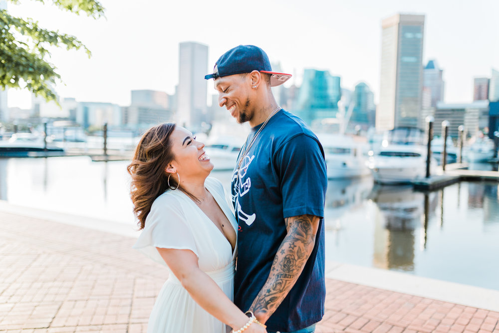 couple laughing together during their engagement session in downtown baltimore