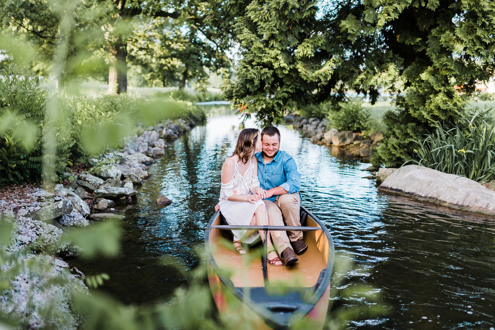 bride kissing groom on cheek in canoe during their md engagement session
