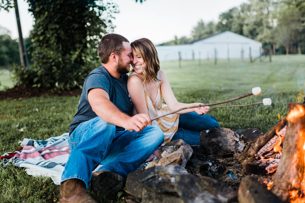 couple laughing during their bonfire engagement session with smores in maryland