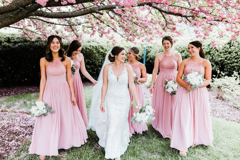 bride laughing and walking with her bridesmaids - pink gowns - maryland wedding photographer
