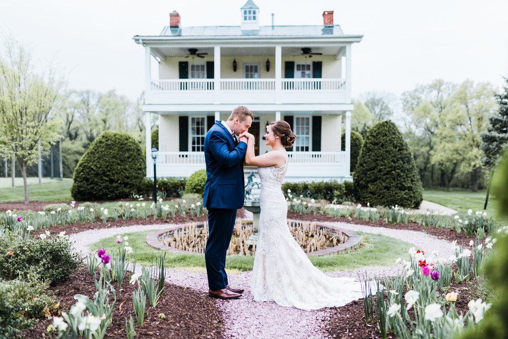 groom kissing brides hands in garden estate wedding maryland wedding photographer