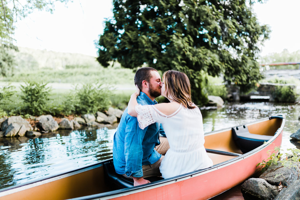 bride and groom kissing in canoe at md engagement session