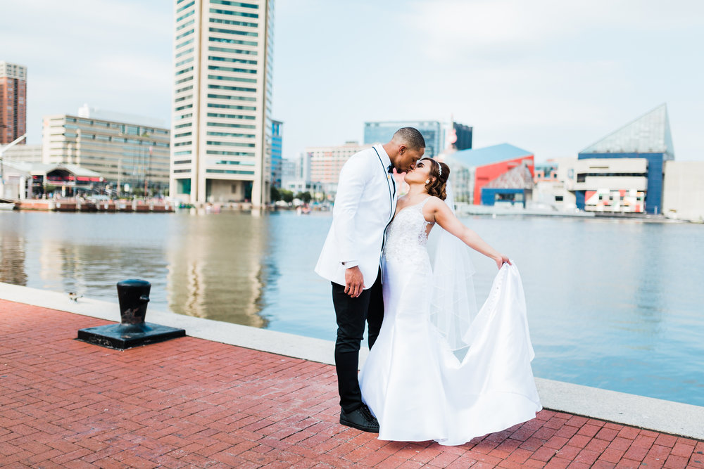 bride and groom kiss by the water at the inner harbor - maryland wedding photographer and cinematographer