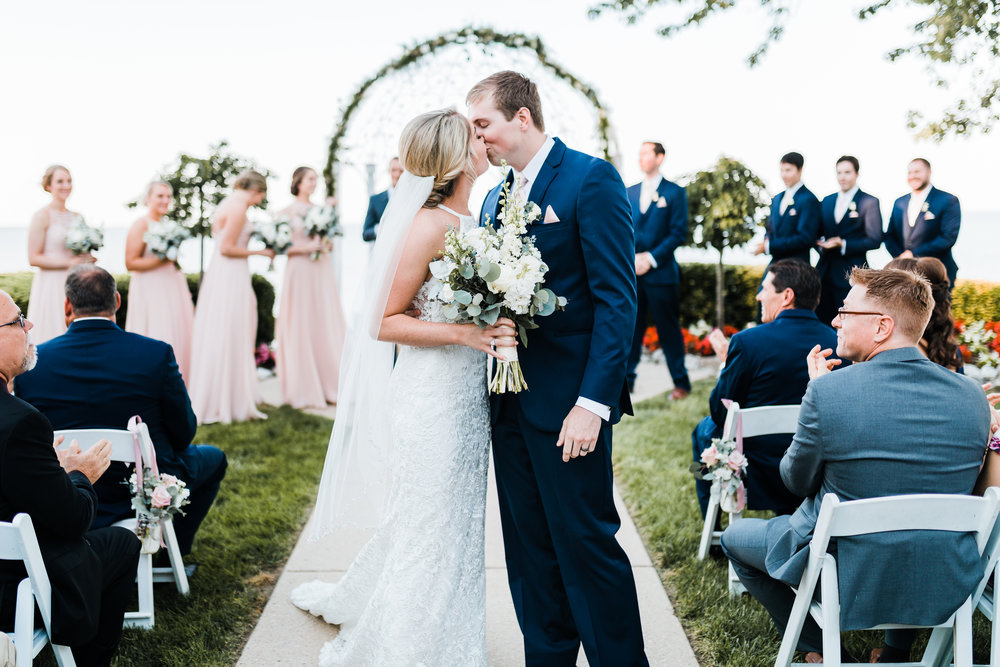 bride and groom kiss one more time as they come back down the aisle - md wedding photographer - husband and wife team