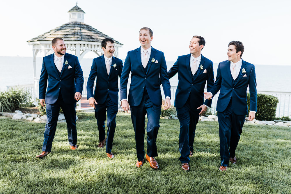 groom laughing and walking with his groomsmen in navy blue suits with light pink ties - maryland wedding photographer