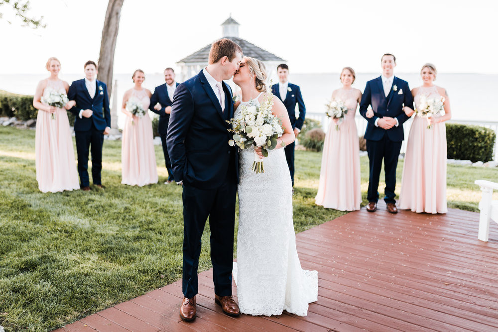bride and groom kiss with bridal party in the background - pasadena maryland
