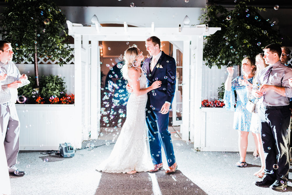 bride and groom celebrate their grand exit with bubbles at celebrations at the bay - md wedding photographer and cinematographer