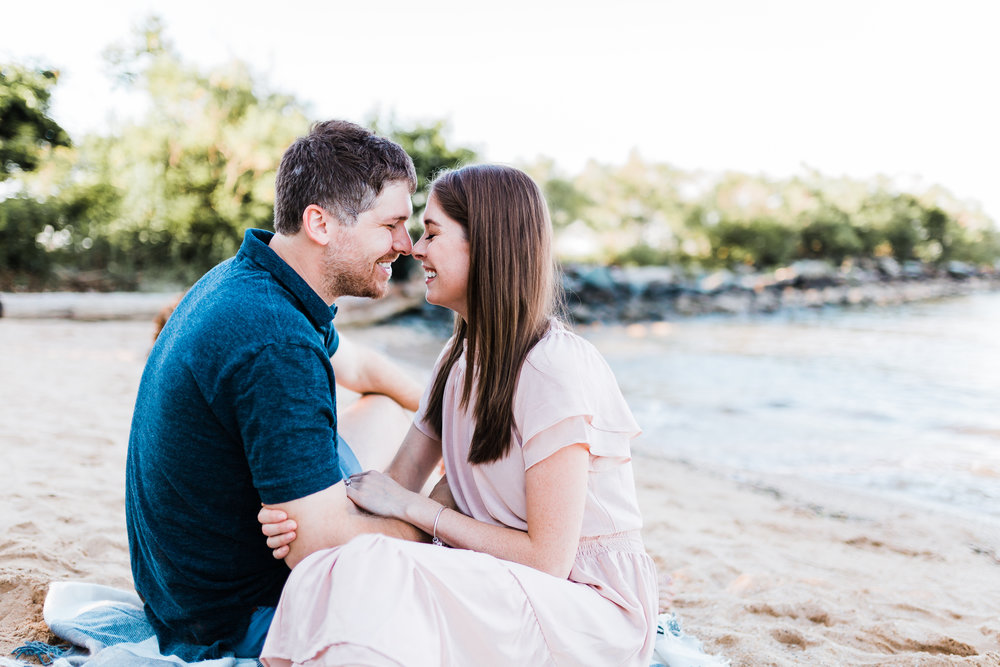 couple snuggling on the beach in maryland for their engagement session - md wedding photographer