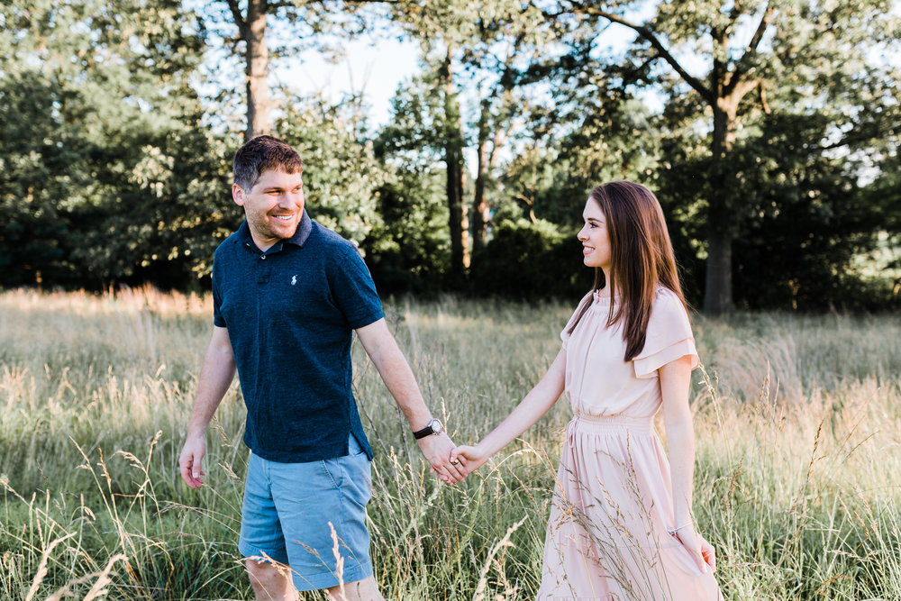 couple holding hands and walking in high grasses - romantic maryland engagement photos - pasadena maryland photographer
