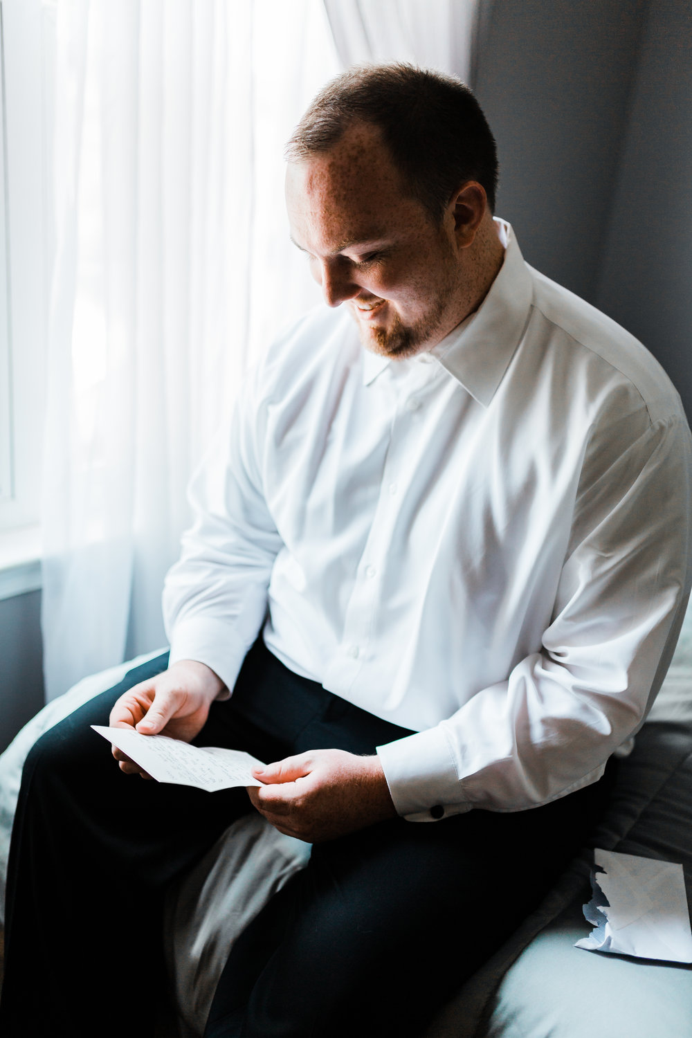 groom getting ready and reading his letter from his bride - pasadena maryland wedding photographer and cinematographer