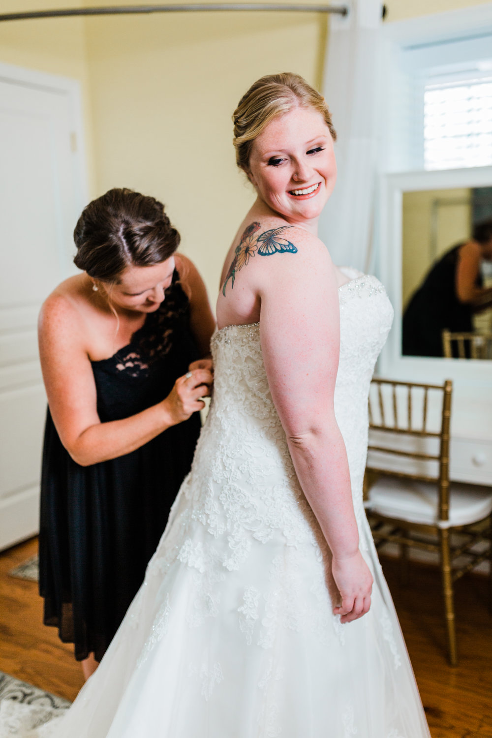 bride with her matron of honor getting her dress on - kurtz's beach wedding - maryland wedding photographer