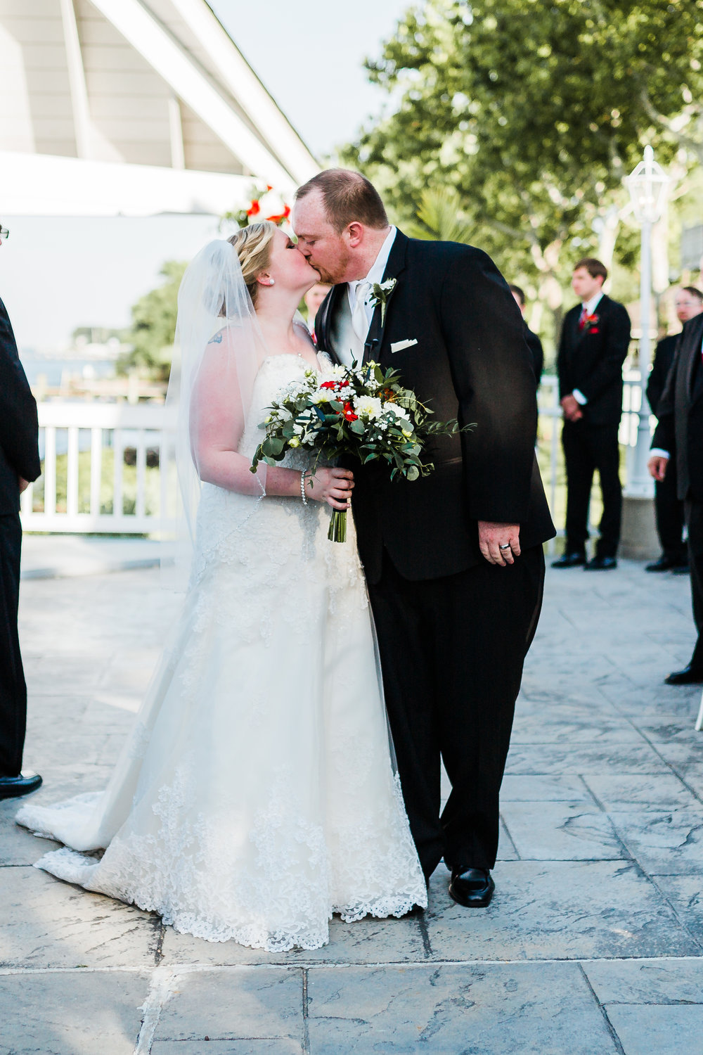 bride and groom kiss after saying i do - maryland wedding ceremony - waterfront wedding venues in md - top md photographer and videographer