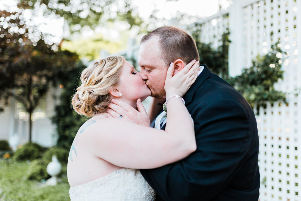bride and groom kiss romantically on their wedding day - kurtz's beach - md wedding photographer and videographer