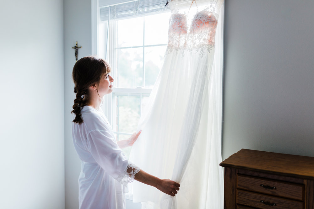 bride admiring her wedding dress - md wedding photo and video