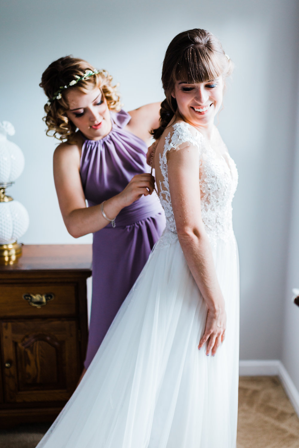 bride getting her dress on with her maid of honor - md wedding photographer