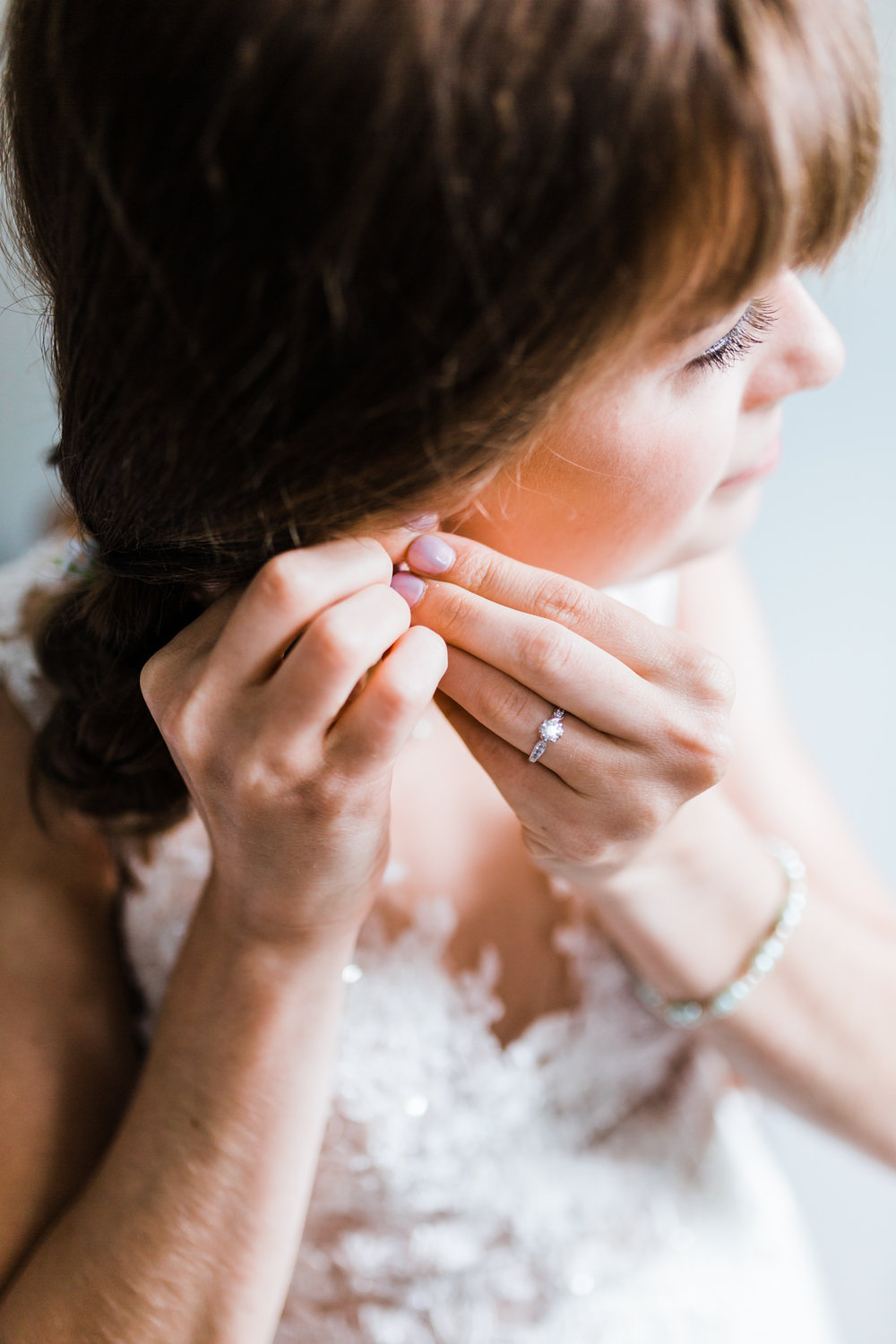bride putting on her pearl earrings for her wedding in maryland