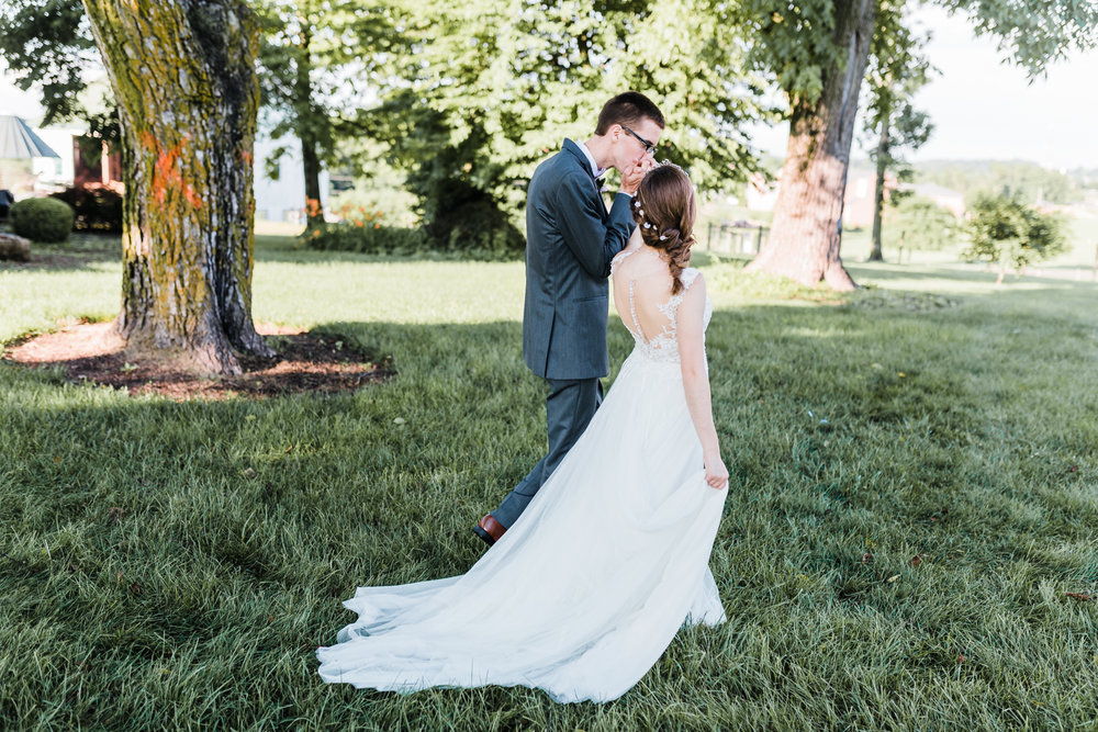 groom kissing his bride's hand as they walk together - md wedding photographer