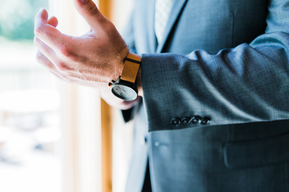 groom getting ready and adjusting his watch at Liberty Mountain Resort - Pennsylvania weddings
