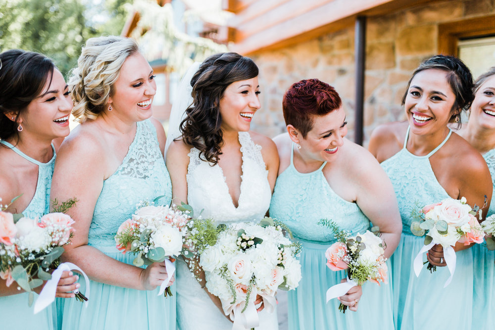 bride and bridesmaids laughing - silver dollar eucalyptus - peach roses - bridal bouquet - top rated MD wedding photographer