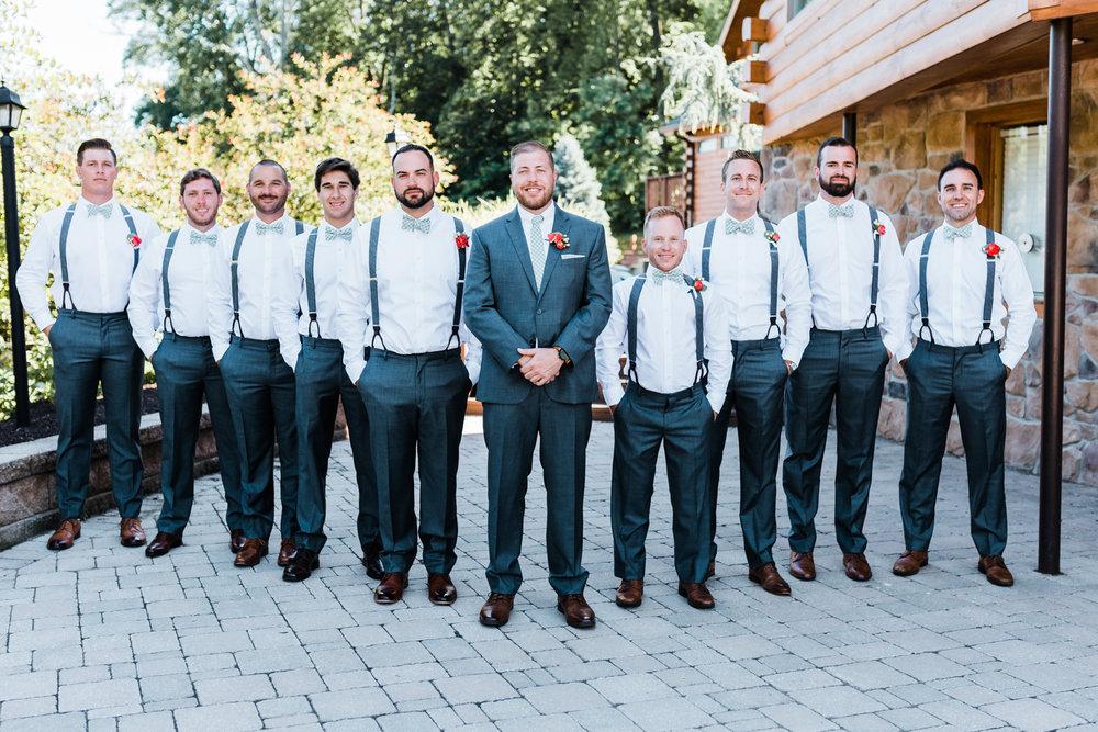 groom with his groomsmen - suspenders at wedding - mountain weddings - large party of groomsmen