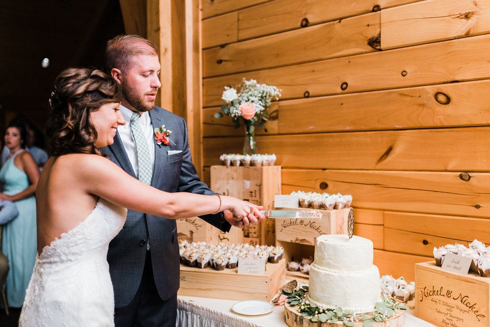 bride and groom cut the cake together - best md wedding photographer and videographer