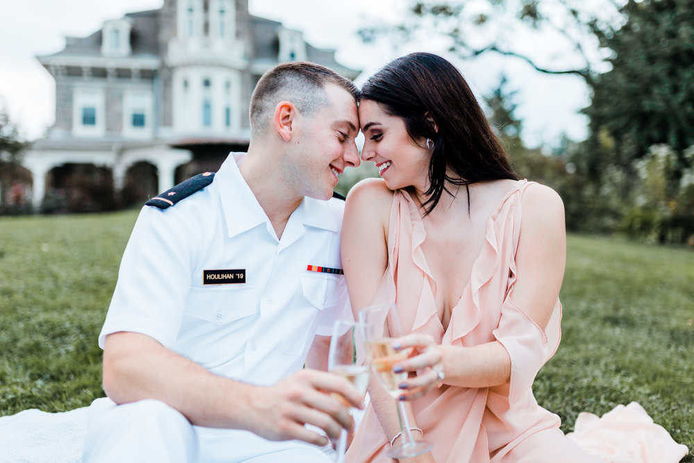 couple sharing champagne on the lawn of cylburn arboretum - engagement sessions with champagne