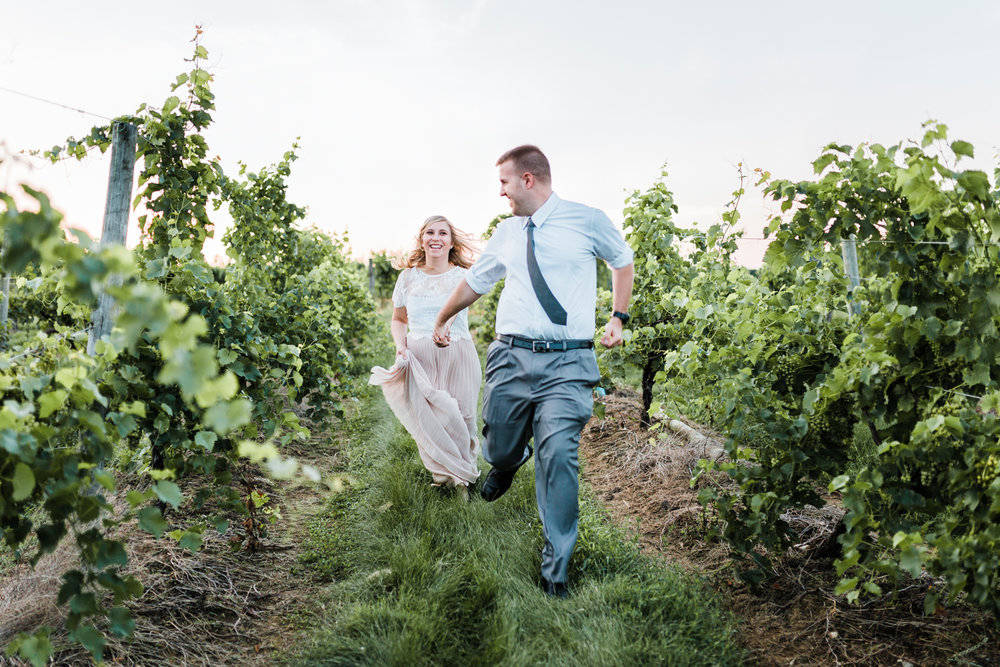 couple romantically running through vineyard during golden hour - top md wedding and engagement photographer